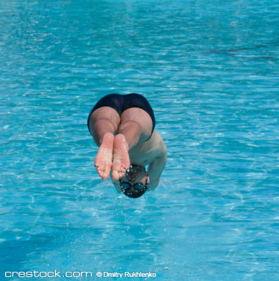 Swimmer jumping into blue water